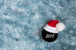 Hockey black washer in a Santa cap with an inscription 2018 close-up on a blue background with copy space flat lay