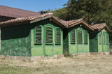 Old vintage obsolete abandoned green wooden camping bungalows in sunny summertime - 181538267