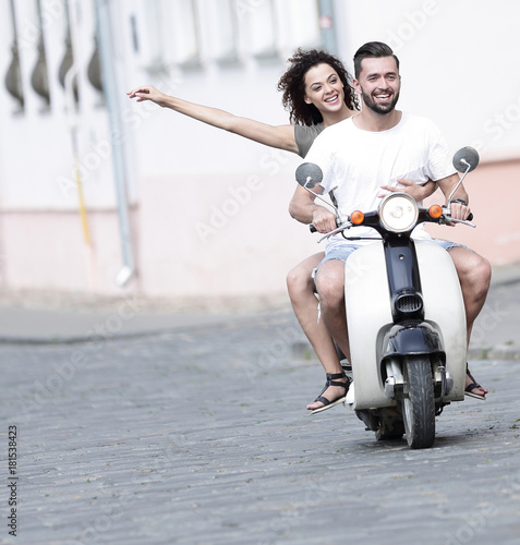 Cool man and beautiful girl riding on scooter with expression