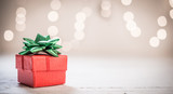 Little red gift box with green ribbon and bokeh light background, copy space - 181538613