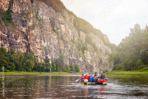 Fotobehang Bergrivier Group of tourists having leisure rafting on inflatable catamaran by river along a rocky shore