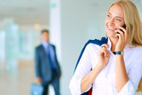 Businesswoman standing against office window talking on mobile phone. Businesswoman - 181552419