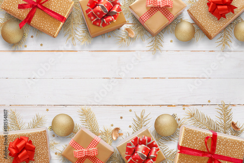 Christmas background with blank space for greeting text. Fir tree branches, gifts and balls lay on white wooden table.