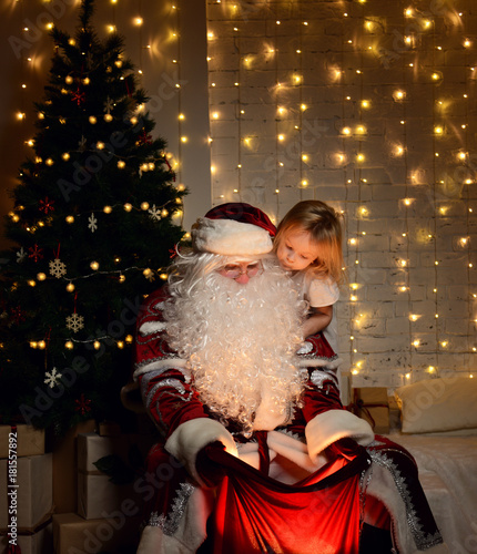 Santa Claus with happy little cute children boy and girl near Christmas tree