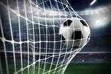 Soccer ball scores a goal on the net - 181563201