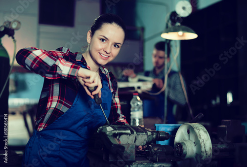 young female who is repairing drill