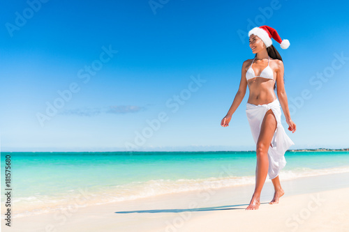 Christmas cruise travel beach vacation holidays in Caribbean destination. Asian bikini woman wearing santa hat on new year holiday relaxing under the tropical sun. Christmas on paradise getaway.