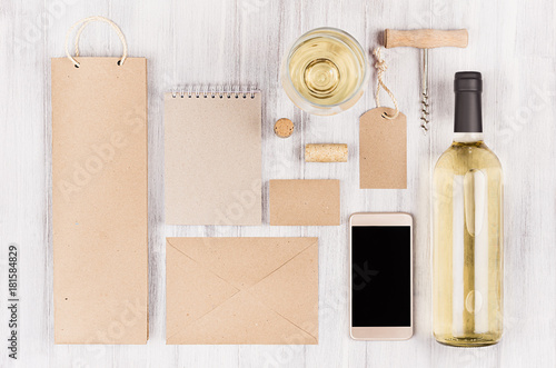 Corporate identity template for wine industry, packaging, stationery, phone, wineglass set with bottle white wine on soft white wood background.