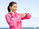 Young woman on beach checking heart rate after run - 181585680