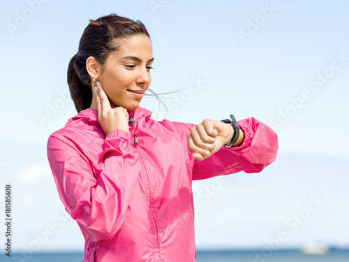 Fotobehang Hardlopen Young woman on beach checking heart rate after run