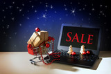 online shopping, christmas baubles and gift boxes in a shopping cart driving out of a laptop with text SALE, dark stars sky background, copy space - 181588627