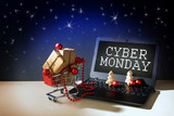 cyber monday online shopping, christmas baubles and gift boxes in a shopping cart driving out of a laptop with text, dark stars sky background, copy space - 181588699