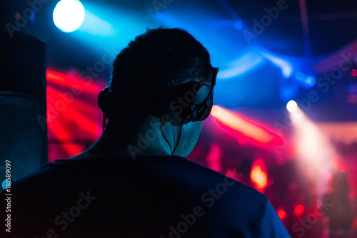 head of DJ with headphones playing back event in night club music
