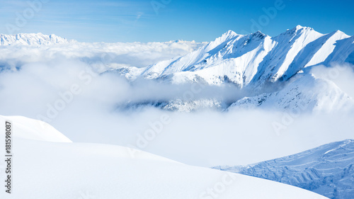 Fototapeta Young, sexy woman is skiing in winter paradise in the alps with a beautiful blue sky and wonderful white snowy mountains