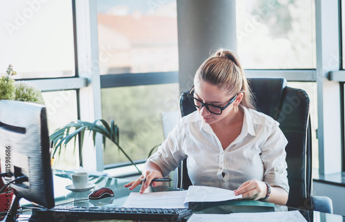 Office worker. Young businesswoman using calculator and laptop for calaulating finance, tax, accounting, statistics and analytic research concept. © steftach