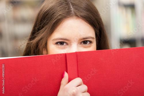Fototapeta Teen looking from behind a book