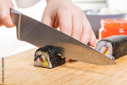 Papiers peints Sushi bar Chef cuts rolls, hands close-up