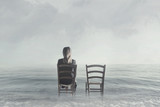 alone woman sitting next to her lover's empty chair - 181612039