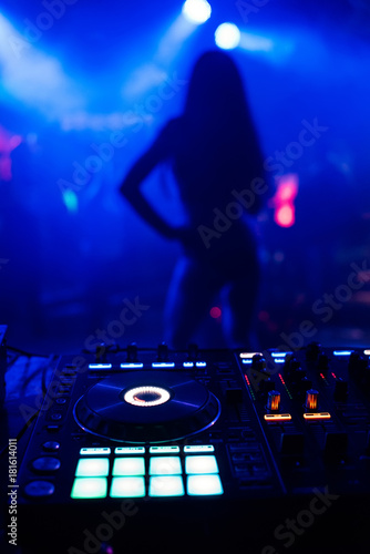 silhouette of young slim dancers on stage out of focus through the DJ booth and Poster