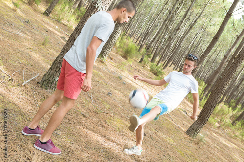 Plexiglas Voetbal Young men playing football in forest