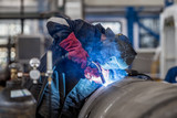 The welder in the mask welds the metal part - 181625428