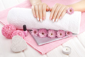 beautiful pink manicure with chrysanthemum flower and towel on the white wooden table. spa