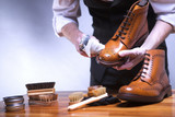The process of cleaning shoes. A man is cleaning his shoes. - 181640252