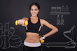 Quadro Maintain healthy way of life. Cheerful content smiling woman holding dumbbells and doing sport exercises while standing in a gym