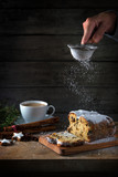 christmas cake, in germany christstollen is sprinkled with icing sugar, coffee cup, spices and cinnamon star cookies on a rustic wooden table, dark vintage background with copy space, vertical - 181648091