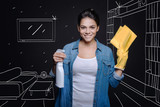 Make it clean. Positive delighted housewife holding wipe and spray while doing spring clean - 181648245