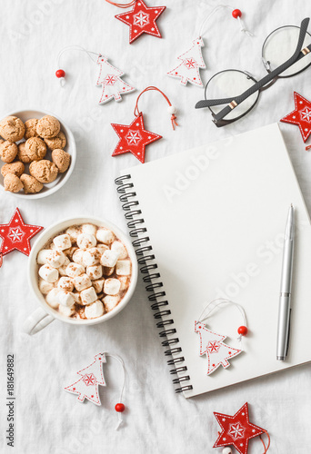 Foto op Canvas Chocolade Hot chocolate with marshmallows and cinnamon, clean blank notepad, christmas decorations on a light background. Christmas inspiration planning concept