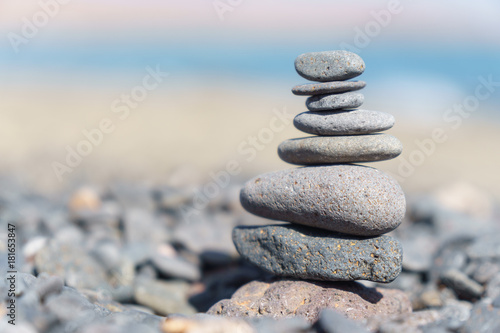 Tuinposter Stenen in het Zand Close-up of stack of stones in perfect balance on a tranquil sunny beach in Fuerteventura, SpainClose-up of stack of stones in perfect balance on a tranquil sunny beach in Fuerteventura, Spain