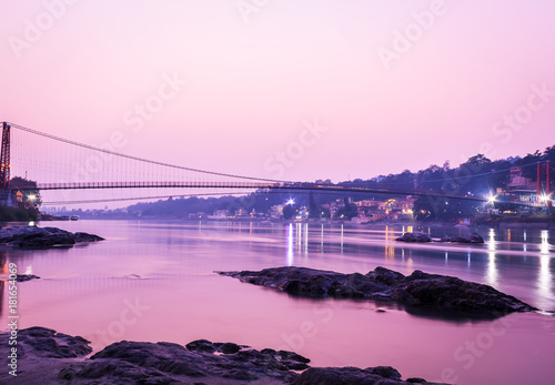 Fotobehang Bruggen View of River Ganges and Ram Jhula bridge after sunset. Rishikesh. India