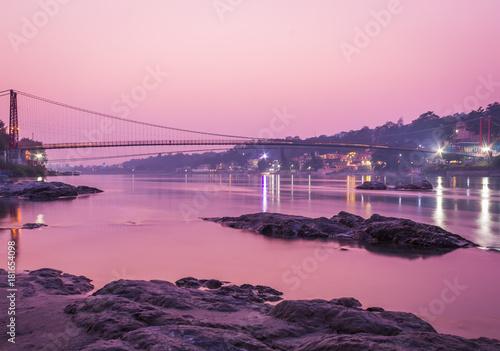 Staande foto Zee zonsondergang View of River Ganges and Ram Jhula bridge after sunset. Rishikesh. India