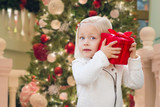 Happy Young Girl Holding Gift Box In Front of Decorated Christmas Tree.