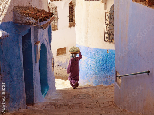 Foto op Plexiglas Marokko A woman caring the bread on her head and walking down the blue-white streets in Chefchaouen - the blue city Morocco - amazing palette of blue and white buildings