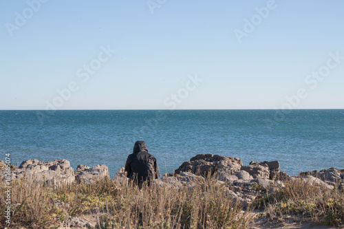 A lonely man covered with a hood is sitting on the rocks on the beach Plakát
