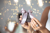 Close up of woman hands holding small gift with ribbon.