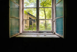 Old double-glazed window in the darkness of the room of an abandoned building