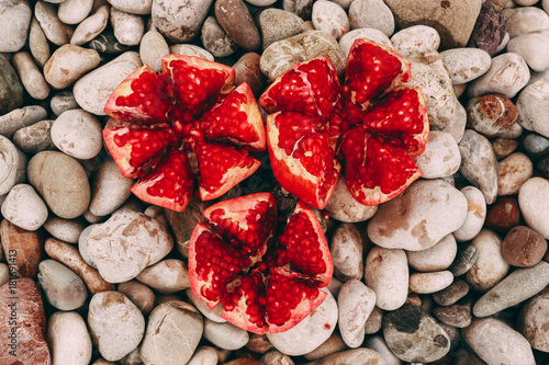 pomegranate on stony background, fruit on the beach close-up