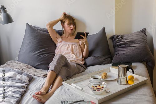 Breakfast and morning news- women reading morning news on her tablet in bed
