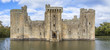 landscape view of Bodiam castle ruins with water surrounded it and blue sky and trees