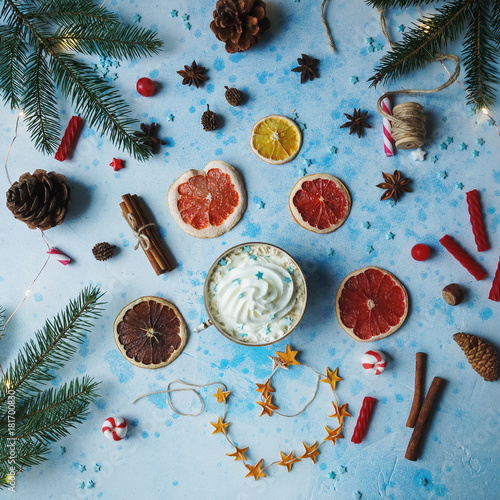 Homemade cocoa or hot chocolate, dried oranges, fir tree, cinnamon, candies on blue concrete background