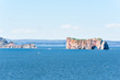 View of Rocher Perce from Bonaventure Island with ocean and gannet birds flying, cityscape skyline or coastline of city
