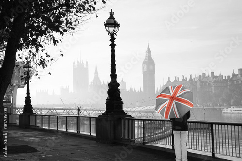 UK - Cities - Palace of Westminster in fog seen from South Bank, one Tourist with Union Jack Umbrella Present