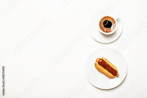 Poster Eclairs cake and espresso coffee with foam, white background, top view