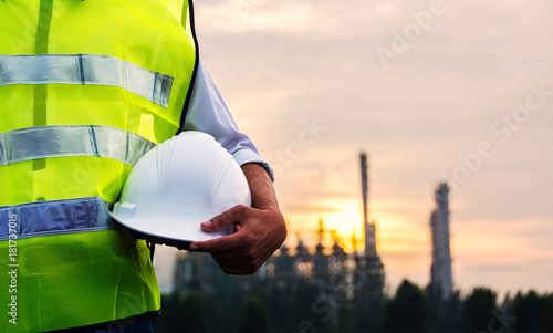 Engineer or Safety officer holding hard hat with Petrochemical plant
