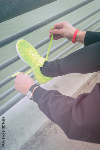 mata magnetyczna Urban jogger tying running shoes on a fence from the bridge above the river.