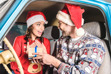 man sharing christmas gift to woman