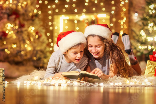 Foto Murales Two children on the floor read a book in a room decorated with Christmas decorations.